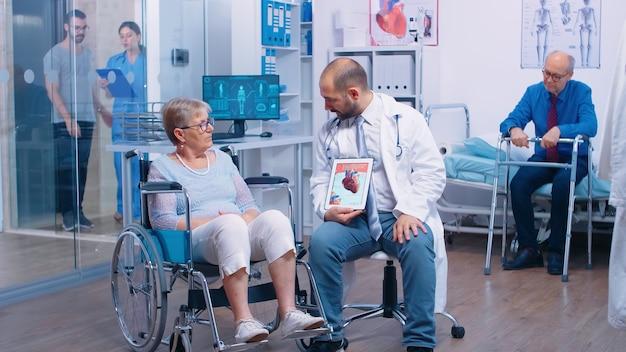 Explicação da doença arterial coronariana de um médico a uma mulher idosa aposentada com deficiência em cadeira de rodas em uma clínica de recuperação. pacientes idosos com andador, deficiência física no hospital, anúncio médico