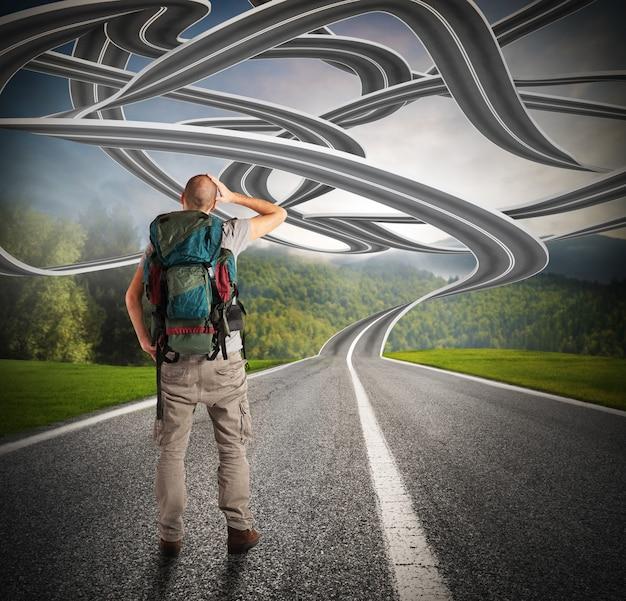 Explorador confuso diante de uma estrada sinuosa