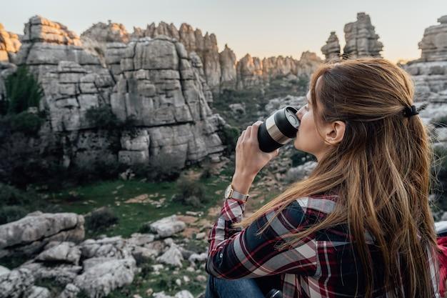 Explorador da jovem mulher que bebe o café de uma garrafa térmica com as montanhas no fundo. conceito de aventura, excursões e viagens.