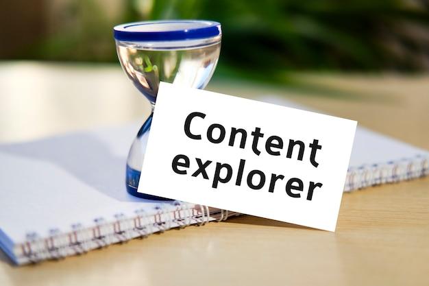 Explorador de conteúdo - texto de conceito de business seo em um caderno branco e um relógio de ampulheta, folhas verdes de flores