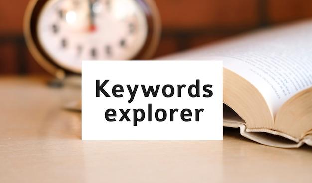 Explorador de palavras-chave - texto de conceito de negócios de seo em um caderno branco e relógio, livro