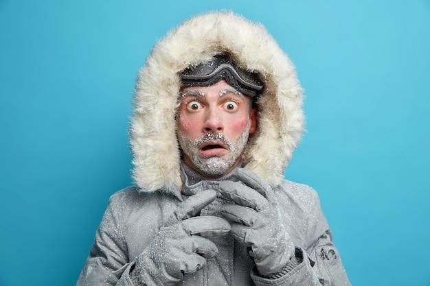 Explorador masculino congelado tem o rosto vermelho coberto de olhares congelados muito chocado surpreso com a temperatura muito baixa usa uma jaqueta quente e luvas caminha ao ar livre durante o tempo frio da nevasca