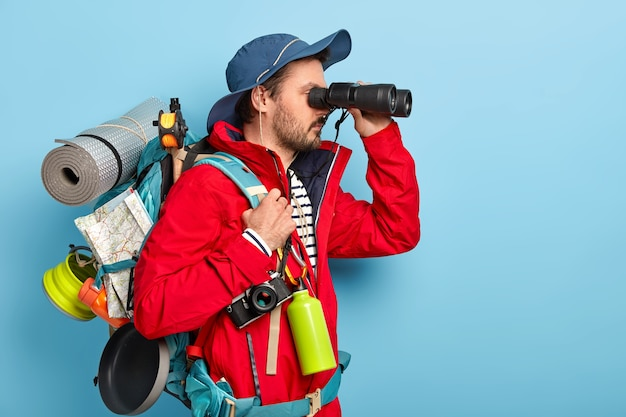 Explorador masculino vestido com roupa casual, com binóculos perto dos olhos, usa chapéu e jaqueta, faz caminhadas nas montanhas