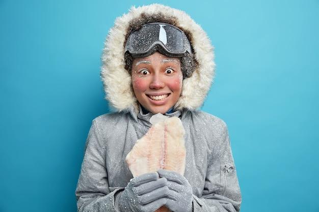 Exploradora polar feminina vai pescar no gelo durante o inverno, vestida com agasalhos, segura peixes congelados vestidos com roupas confortáveis sobre a parede azul que treme durante os dias frios, preparada para as mudanças climáticas