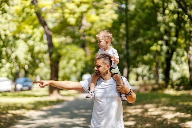 Explorando a natureza, pai e filho brincam no parque o pai carrega o filho nos ombros e caminham pelo parque em um dia ensolarado de verão vestidos com as mesmas roupas, pai aponta para algo