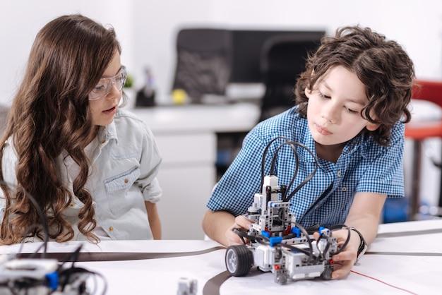 Explorando novas tecnologias. crianças curiosas e atenciosas sentadas na escola e tendo aulas de ciências enquanto expressam curiosidade