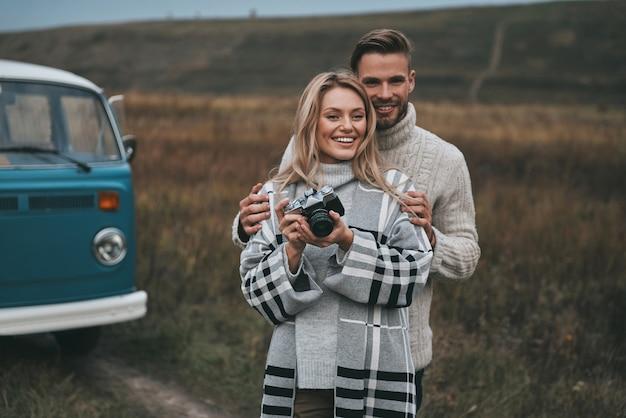 Explorando o mundo juntos. mulher jovem e bonita desviando o olhar e sorrindo enquanto ficava ao ar livre com o namorado