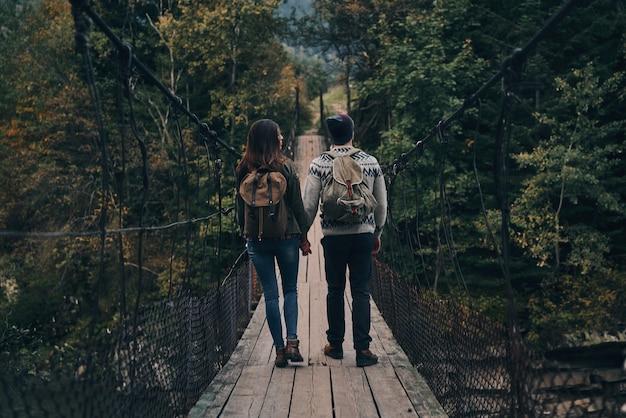 Explorando o mundo juntos. retrovisor de corpo inteiro de um jovem casal de mãos dadas enquanto caminha na ponte pênsil