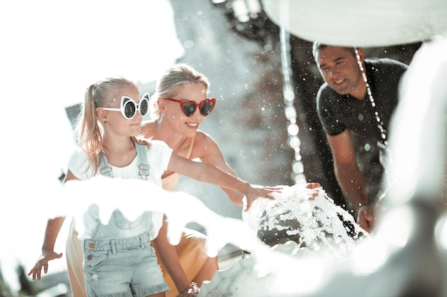 Explorando o novo. menina séria e a mãe dela colocando as mãos na fonte na frente de seu pai.