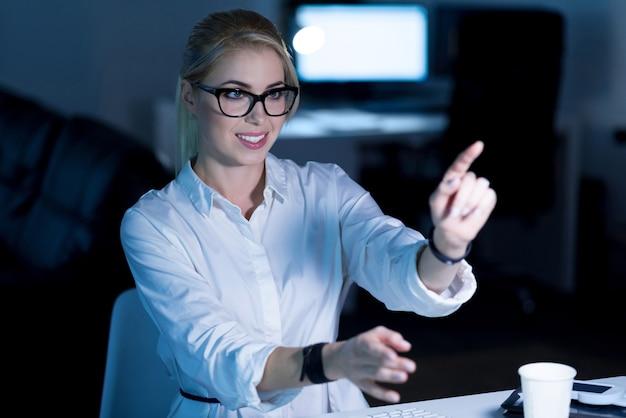 Explorando tecnologias de ti. agradável jovem profissional de ti sentada no escritório e usando tecnologias modernas enquanto expressa interesse