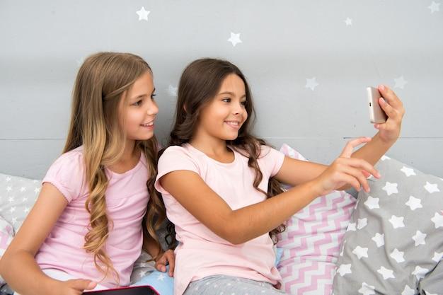Explore a rede social. smartphone para entretenimento. crianças tirando selfie. conceito de aplicativo do smartphone. entretenimento online. festa do pijama de lazer feminino. meninas de smartphones pequenos blogueiros.