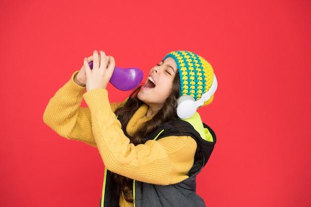 Explore o potencial da sua voz. criança pequena faz vocal em fundo vermelho de escova de microfone. a menina gosta de cantar a melodia vocal. treinar suas habilidades vocais. canção de karaokê, copie o espaço.
