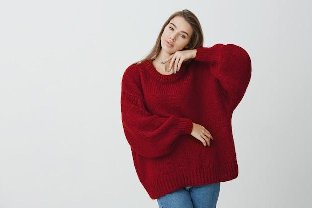 Explore sua sensualidade. foto de estúdio de incrível mulher esbelta europeia, inclinando a cabeça e tocando com ternura o rosto com a mão, posando para o comercial na camisola de inverno.
