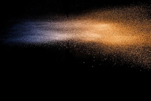 Explosão alaranjada azul das partículas de poeira no fundo preto. respingo de pó de pó de cor.