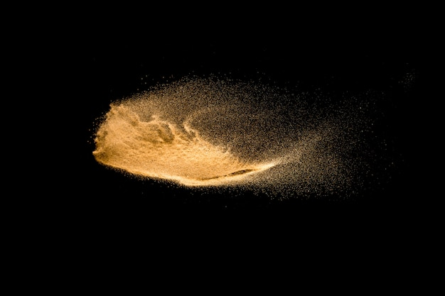 Explosão amarela da areia isolada no fundo preto.