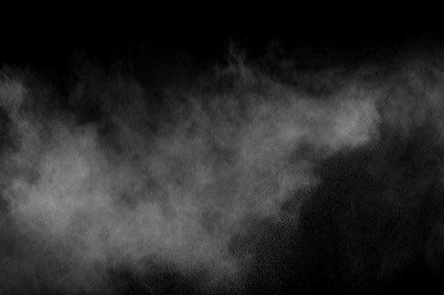Explosão branca abstrata do pó contra o fundo preto a poeira branca expira no ar.