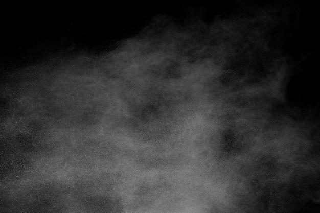 Explosão branca do talco que espirra no fundo preto.