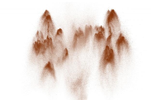 Explosão de areia de rio seco. respingo da areia de cor castanha contra o fundo branco.