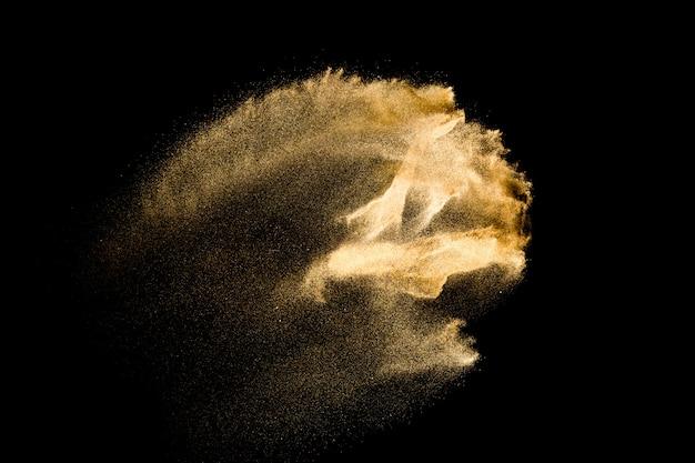 Explosão de areia de rio seco. respingo dourado da areia da cor de encontro ao fundo preto.