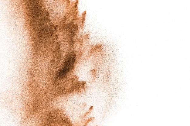 Explosão de areia do rio seco. respingo de areia cor marrom contra fundo branco.