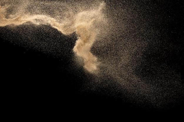Explosão de areia do rio seco. respingo de areia de cor marrom contra fundo preto.