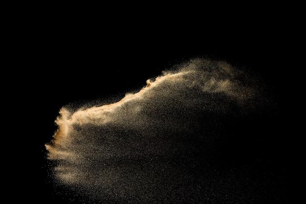 Explosão de areia dourada isolada no fundo preto. nuvem de areia abstrata.