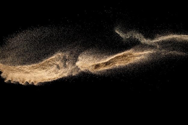 Explosão de areia marrom isolada no fundo preto. congele o movimento de respingos de poeira arenosa.