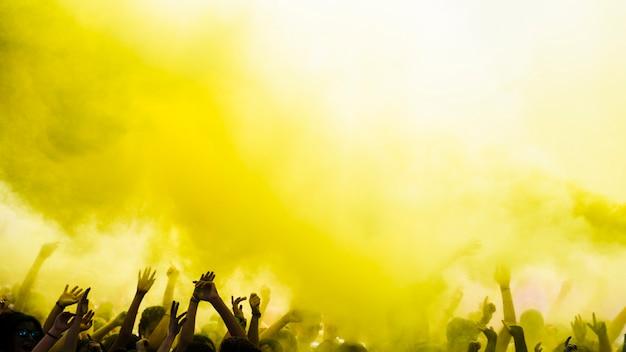 Explosão de cor holi amarelo sobre a multidão