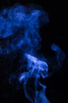 Explosão de fumaça azul contra o fundo preto