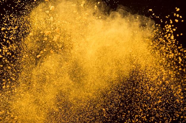 Explosão de laranja de pó cosmético em fundo escuro
