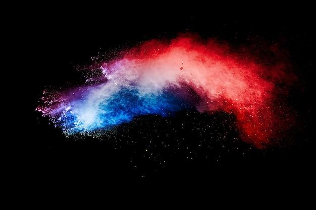 Explosão de partículas de poeira azul vermelha em fundo preto. respingo de pó azul vermelho.