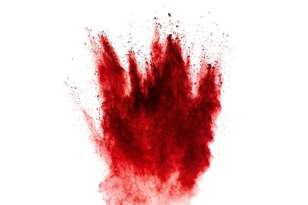Explosão de partículas de poeira vermelha em fundo branco.