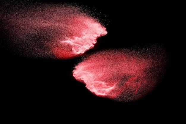 Explosão de partículas vermelhas em fundo preto.