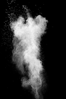 Explosão de pó branco isolada em fundo preto. respingo de partículas de poeira branca.