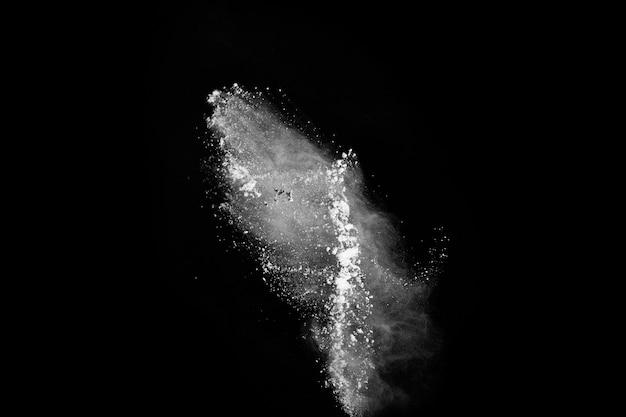 Explosão de pó branco sobre fundo preto. nuvem colorida. poeira colorida explodir.