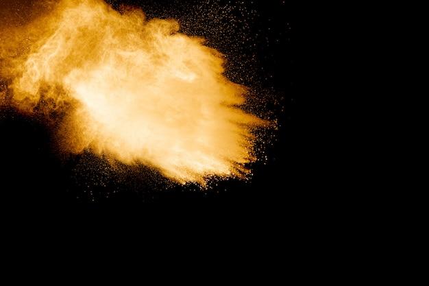 Explosão de pó de cor laranja em fundo preto. respingo de poeira de cor laranja.