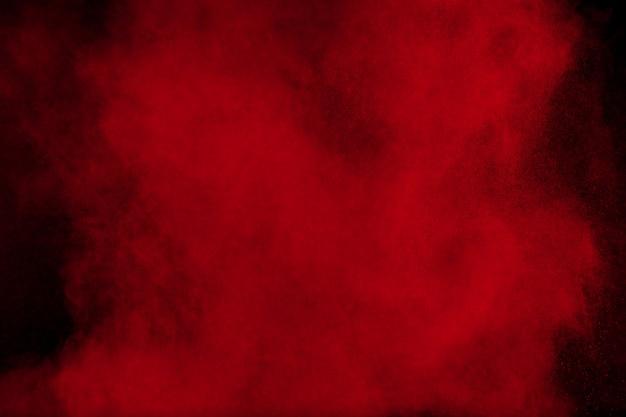 Explosão de pó de cor vermelha em preto