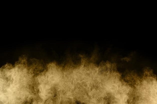 Explosão de pó dourado em fundo preto. congelar movimento.