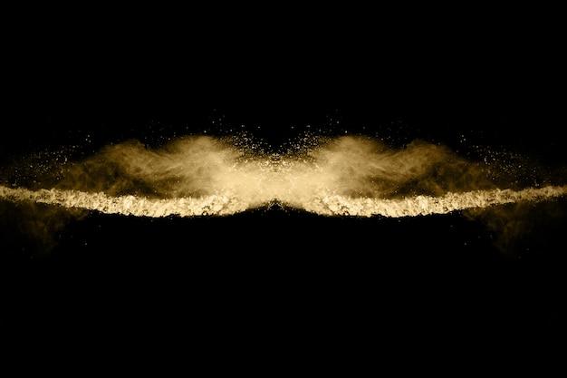 Explosão de pó dourado em fundo preto. congele o movimento.