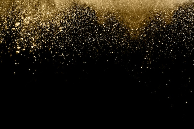 Explosão de pó dourado sobre fundo preto.