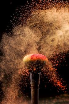 Explosão de pó e pincel de maquiagem em fundo escuro