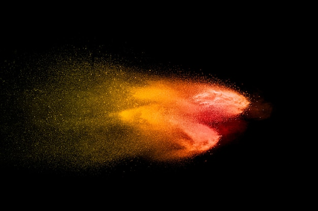 Explosão de pó laranja e vermelho no escuro