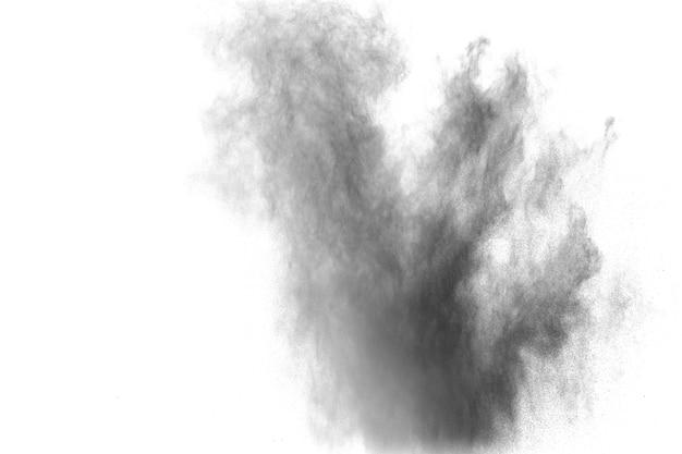 Explosão de pó preto. as partículas de respingos de carvão no fundo branco