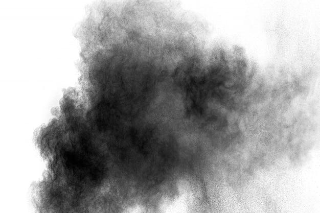 Explosão de pó preto sobre fundo branco. partículas de poeira de carvão nuvem no ar.