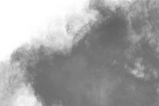 Explosão de pó preto sobre fundo branco.