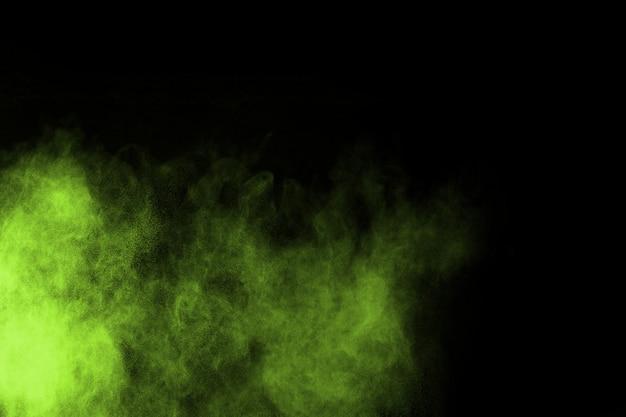 Explosão de poeira abstrata verde congelado no fundo preto.