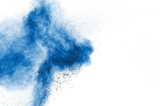 Explosão de poeira azul abstrata no fundo branco. congelar o movimento de salpicos de partículas azuis.