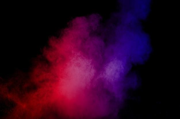 Explosão de poeira azul vermelha abstrata no fundo preto.