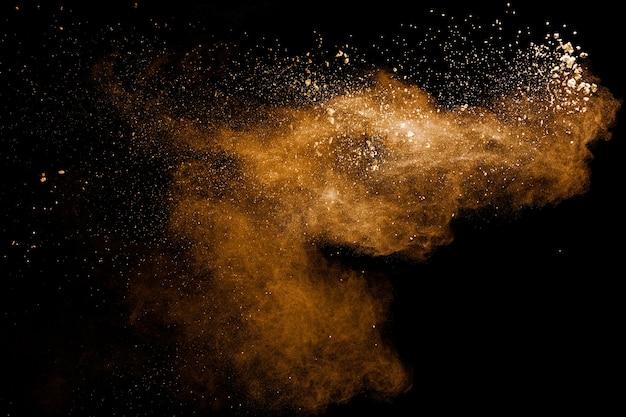 Explosão de poeira marrom abstrata em fundo preto salpicos de pó marrom