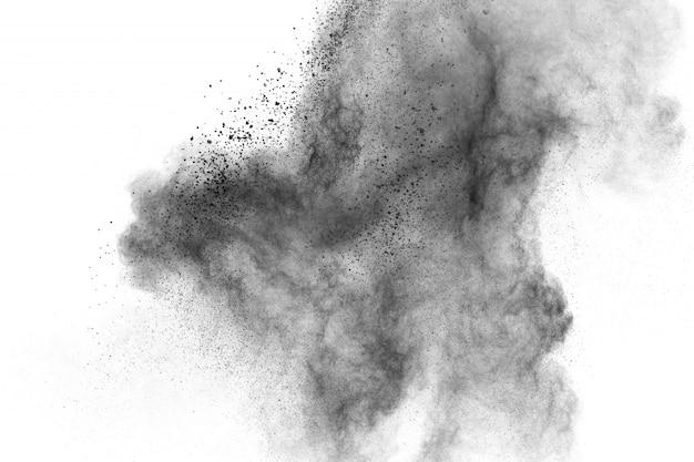 Explosão do pó preto de encontro ao fundo branco. partículas de poeira de carvão exalam no ar.
